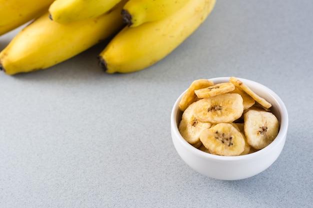 Gebackene bananenchips in einer weißen schüssel und ein bündel bananen auf dem tisch. fast food. nahansicht. vertikale ansicht. speicherplatz kopieren