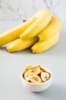 Gebackene bananenchips in einer weißen schüssel und ein bündel bananen auf dem tisch. fast food. nahansicht. vertikale ansicht