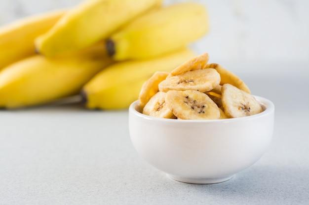 Gebackene bananenchips in einer weißen schüssel und ein bündel bananen auf dem tisch. fast food. nahansicht