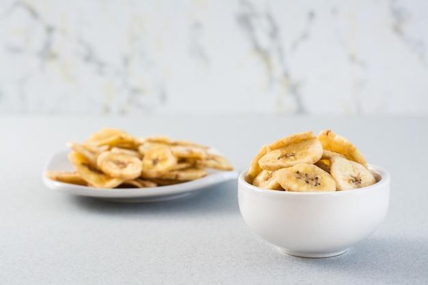 Gebackene bananenchips in einer weißen schüssel und untertasse auf dem tisch. fast food. speicherplatz kopieren