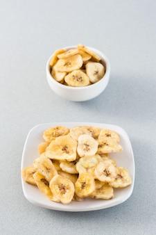 Gebackene bananenchips in einer weißen schüssel und untertasse auf dem tisch. fast food. web-banner. vertikale ansicht