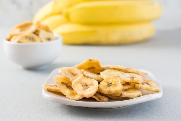Gebackene bananenchips in einer weißen schüssel und untertasse und ein bündel bananen auf dem tisch. fast food.