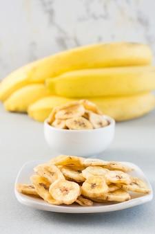 Gebackene bananenchips in einer weißen schüssel und untertasse und ein bündel bananen auf dem tisch