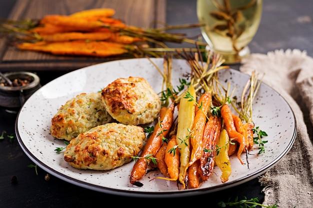 Gebackene bio-karotten mit thymian und schnitzel / frikadelle hühnerfleisch und zucchini. diätessen.