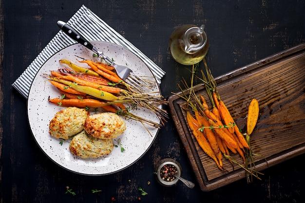 Gebackene bio-karotten mit thymian und schnitzel / frikadelle hühnerfleisch
