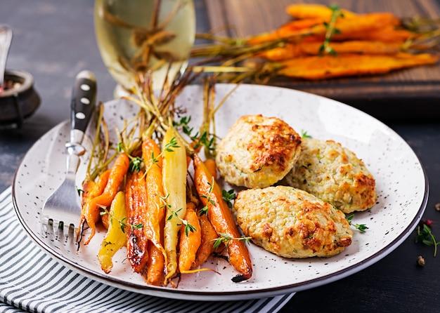 Gebackene bio-karotten mit thymian und schnitzelhähnchen mit zucchini