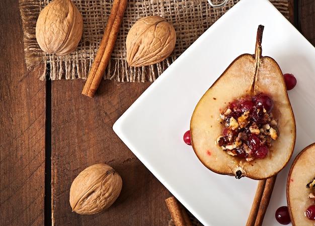 Gebackene birnen mit preiselbeeren, honig und walnüssen