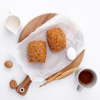 Gebackene brötchen auf hölzernem brett mit tasse kaffee