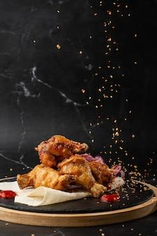 Gebackene buffalo chicken wings mit sesam, zwiebeln und chili-scheiben auf schwarzem holzbrett.