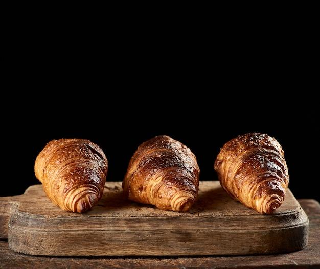 Gebackene croissants auf braunem küchenbrett mit kopierraum