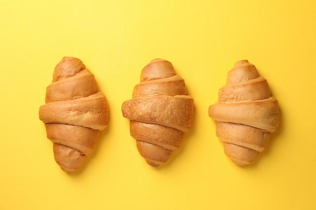 Gebackene croissants auf gelbem hintergrund, draufsicht