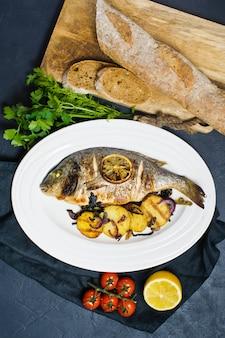 Gebackene dorado-fische auf einer weißen platte, schmücken bratkartoffeln.