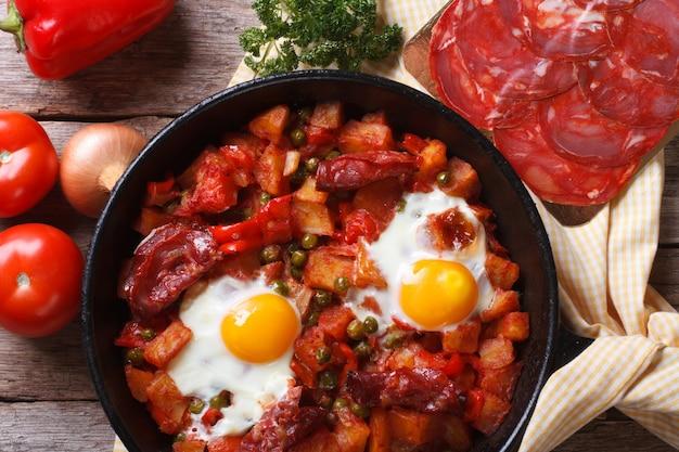Gebackene eier mit chorizo und gemüse in der pfanne