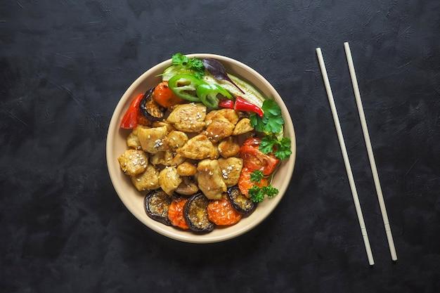 Gebackene fleischstücke mit gegrilltem gemüse auf einem teller. chinesische küche.