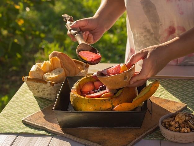Gebackene früchte und beeren in einem kürbis. essen auf die natur. das konzept. gesundes essen