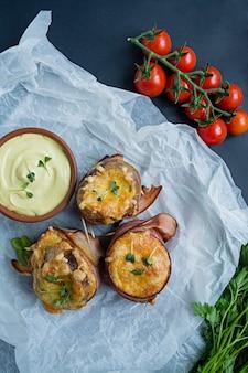 Gebackene frühkartoffeln im speckmantel, dazu käse, sauce und frisches gemüse.