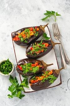 Gebackene gefüllte auberginen mit verschiedenem gemüse, tomaten, pfeffer, zwiebeln und petersilie auf grauem stein- oder betontischhintergrund. ansicht von oben