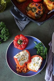 Gebackene gefüllte paprika mit huhn oder pute, mais und kräutern auf keramikplatte.