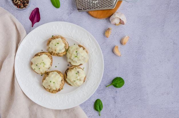 Gebackene gefüllte pilze mit zwiebeln, sahne, knoblauch, thymian und käse auf einem weißen teller. horizontale ausrichtung. draufsicht. speicherplatz kopieren.