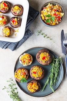 Gebackene gefüllte portobello-pilze mit bulgur-pilaw und gehacktem gemüse.
