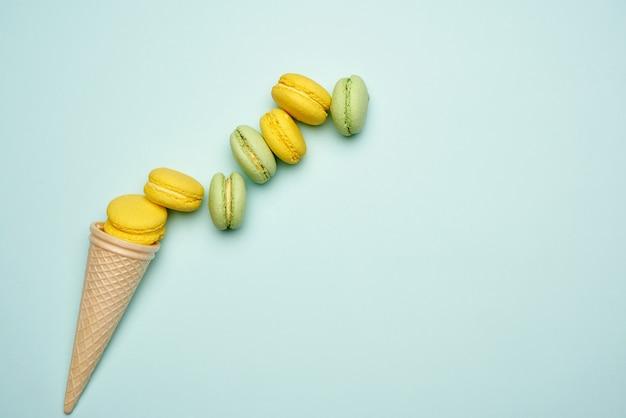 Gebackene gelbe und grüne macarons kekse liegen in einer reihe