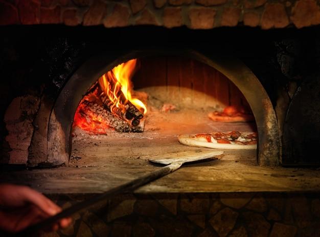 Gebackene geschmackvolle margheritapizza, die den ofen verlässt