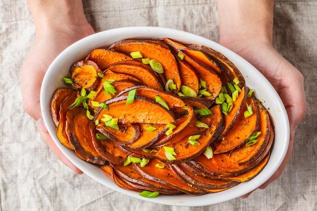 Gebackene geschnittene süßkartoffel mit frühlingszwiebeln in den händen.