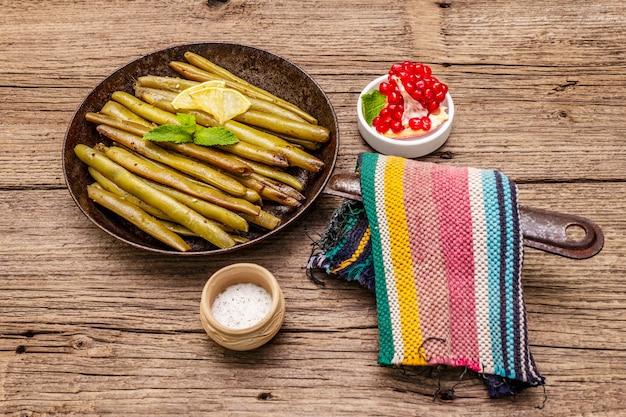 Gebackene grüne bohnen in der pfanne mit sesam, minze und zitrone. gesundes (vegetarisches) lebensmittelkonzept des strengen vegetariers