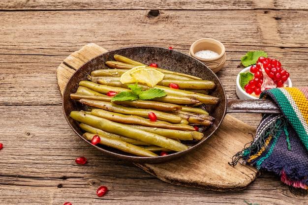 Gebackene grüne bohnen in einer pfanne mit sesam, granatapfel, minze und zitrone