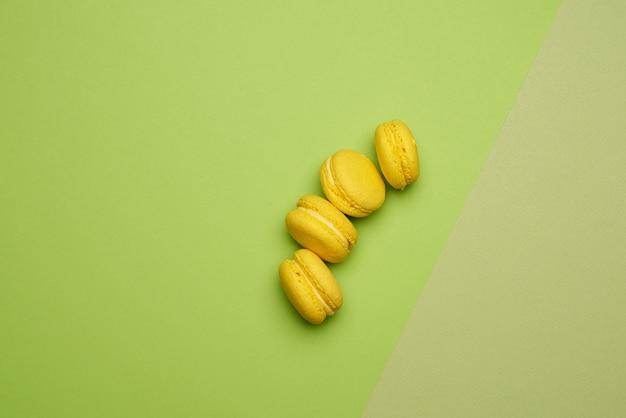 Gebackene grüne macaronsplätzchen liegen in einer reihe auf einem grünen beige hintergrund, draufsicht