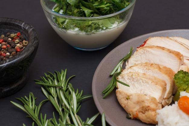 Gebackene hähnchenbrust oder filet auf teller, rosmarin, schalen mit sauce und pimentbeeren auf schwarzem hintergrund. ansicht von oben.