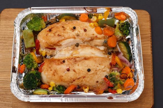 Gebackene hähnchenbrust oder filet mit gemüse und gemüse in metallbehälter auf einem holzbrett. ansicht von oben.