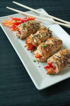 Gebackene hähnchenbrustbrötchen mit kräutern, karottenscheiben, paprika auf einem dunklen schneidebrett. asiatischer stil. das gleichgewicht zwischen gesunder ernährung. kochen. dunkler hölzerner hintergrund.