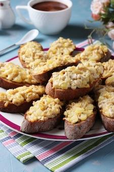 Gebackene hausgemachte toasts mit hühnchen, käse, ananas und knoblauch sowie tasse kaffee auf hellblauem hintergrund. hochformat