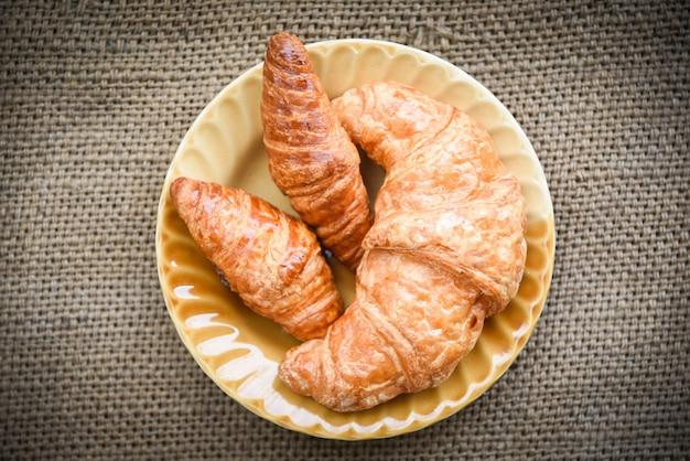 Gebackene hörnchen - bäckereibrot auf selbst gemachtem frühstücksnahrungskonzept des sacks in der tabelle