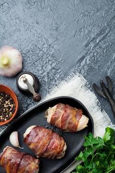 Gebackene hühnerbrust in speck gewickelt auf einer gusseisernen pfanne auf einem schwarzen