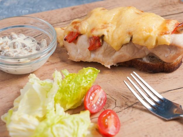 Gebackene hühnerbrust mit käse auf roggenbrot mit pilzsauce