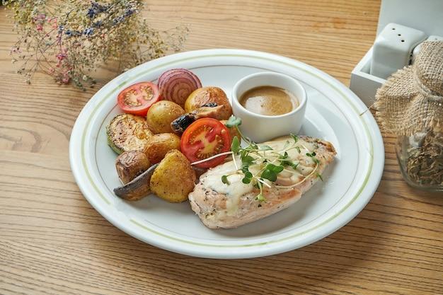 Gebackene hühnerbrust mit käse, garniert mit jungen kartoffeln und anderem gemüse in einem weißen teller. gesunde ernährung
