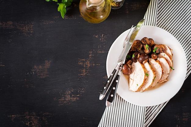 Gebackene hühnerbrust mit pilzen in der balsamico-sauce auf dem tisch. ansicht von oben