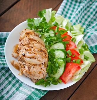 Gebackene hühnerbrust und frisches gemüse auf dem teller