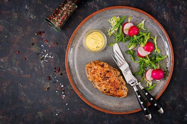 Gebackene hühnerbrust und frischgemüse auf der platte auf einer dunkelheit. diätmenü. flach liegen. ansicht von oben
