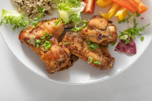 Gebackene hühnerflügel auf weißem hintergrund. ein produkt mit hohem eiweißgehalt und karamellisierten fetten.
