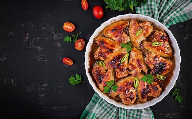 Gebackene hühnerflügel im asiatischen stil auf auflaufform. draufsicht über kopf