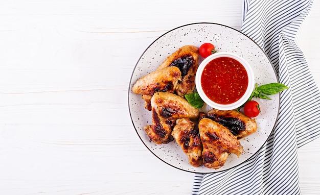 Gebackene hühnerflügel im asiatischen stil und tomatensauce auf teller