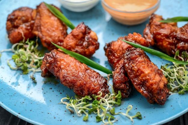 Gebackene hühnerflügel in der asiatischen art auf platte