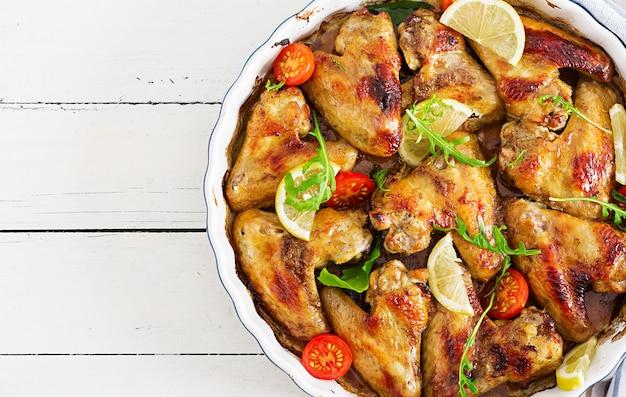 Gebackene hühnerflügel in der platte auf holztisch. ansicht von oben.