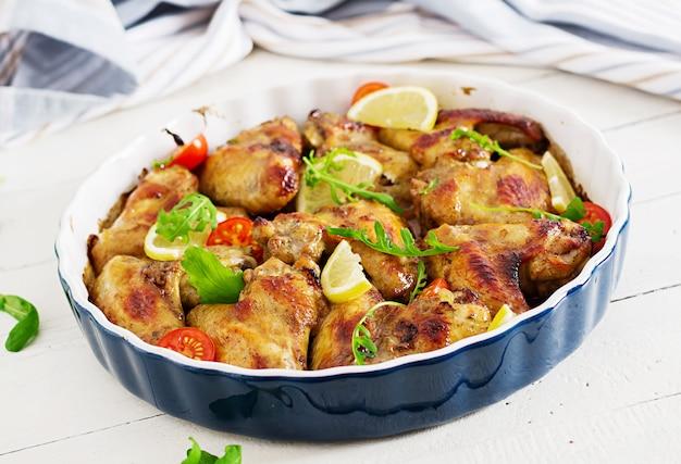Gebackene hühnerflügel in der platte auf holztisch.
