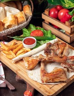 Gebackene hühnerflügel mit pommes-frites im lavash mit gemüse und ketschup auf hölzernem brett