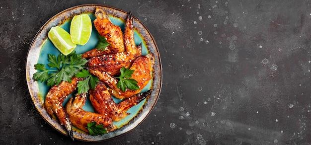 Gebackene hühnerflügel mit sesamsamen, petersilie und kalk auf einem teller draufsicht.