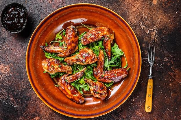 Gebackene hühnerflügel mit süßer chilisauce auf einem teller mit rucola. dunkler tisch. draufsicht.